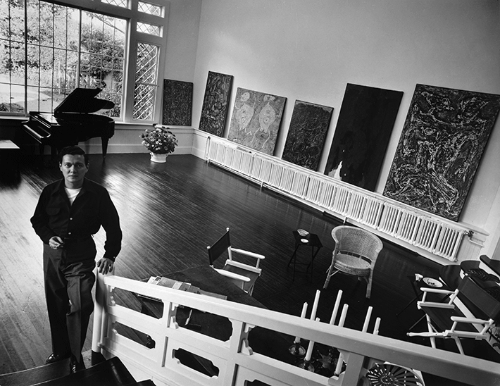 Alfonso Ossorio in the music room at The Creeks,  1952, with paintings by Dubuffet, Still and himself. Photograph by Hans Namuth.