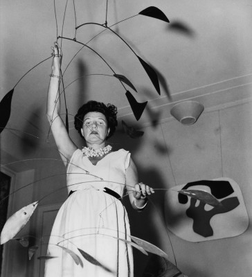 "Peggy Guggenheim with Alexander Calder's ""Arc of Petals"" mobile, and Jean Arp's ""Overturned Blue Shoe"" on the wall behind her."